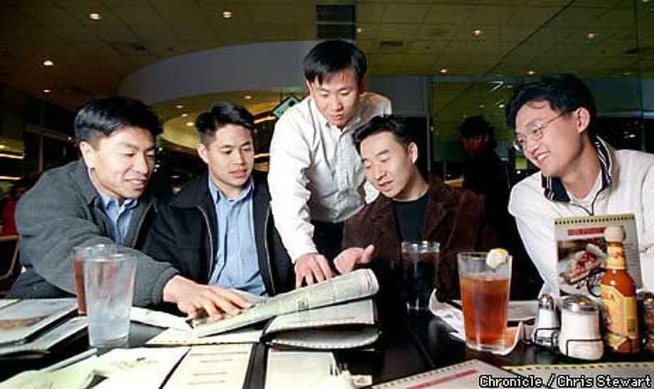 Dan Ho (standing) discussed stocks with fellow investors (from left) Fred Chang, Mark Kanok, Michael Ye and Conrad Kong Chronicle Photo by Chris Stewart