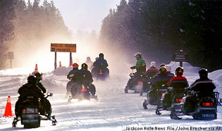 FILE--Persons driving rented snowmobiles jam an entrance to Yellowstone National Park in Wyoming, in this February, 2000 file photo. The snowmobile industry's development of cleaner, quieter machines is a positive step, but does not warrant reversing a proposed ban on their use in Yellowstone and Grand Teton national parks, environmentalists say. The National Park Service has proposed phasing snowmobiles out of Yellowstone and Grand Teton by the winter of 2003-2004. (AP Photo/Jackson Hole News, John Brecher, File) Photo: JOHN BRECHER