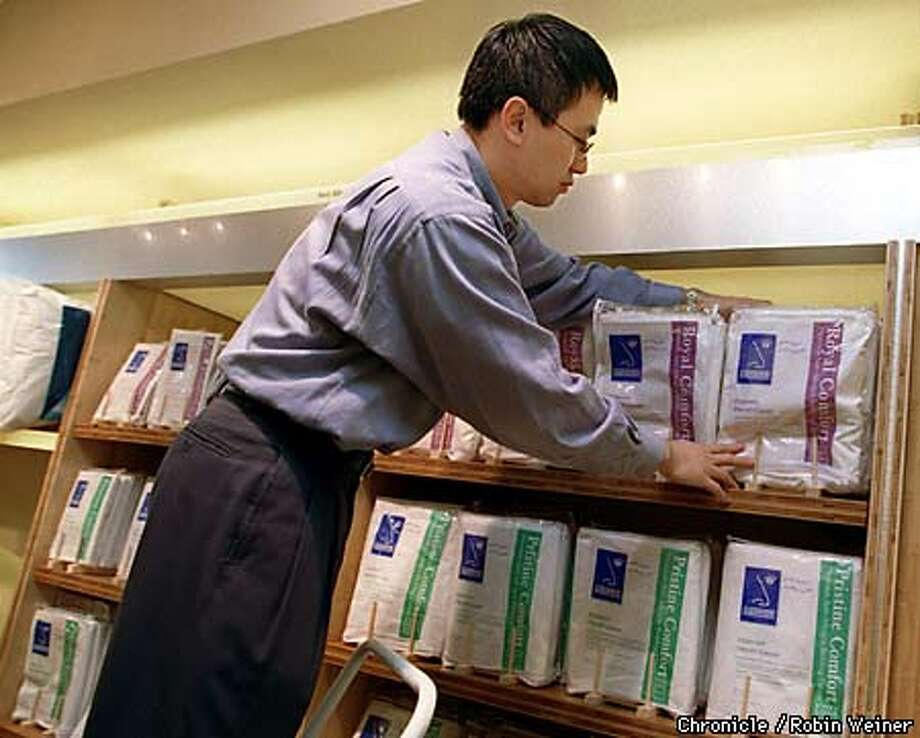 Soon-Chart Yu, CEO of Gazoontite, organizes anti-allergin bedding in the prevention area of his store, which specializes in treating, relieving and preventing allergies. The store, which is located on Union Street, is expected to open during the first week of April.  BY ROBIN WEINER/THE CHRONICLE
