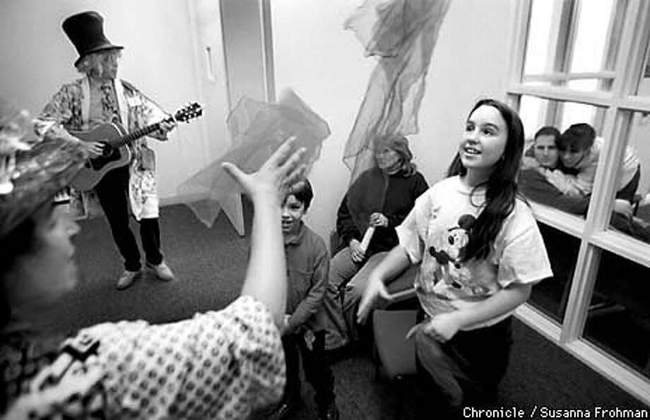 Gina Rose Halpern juggled scarves and Jeff Wright played the guitar for Eddie and Ashley Gonsalves in a waiting room at Mount Diablo Medical Center in Concord. Chronicle Photo by Susanna Frohman