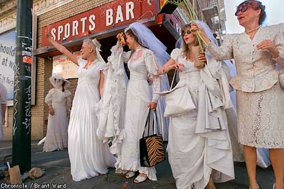 "WEDDING3-18MAR01-SZ-BW--About a hundred dressed in wedding gowns Sunday for the fourth annual ""Brides of March"" march. They gathered at a downtown bar and walked down Geary St. to Union Square. Here they wave to passerby asking if they want a bride. By Brant Ward/Chronicle Photo: BRANT WARD"