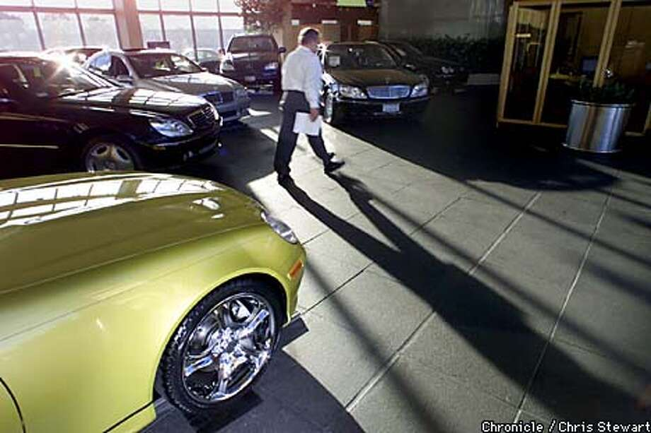 There were lots of cars but no customers as an employee walked through a Mercedes-Benz showroom in Belmont. Chronicle photo by Chris Stewart