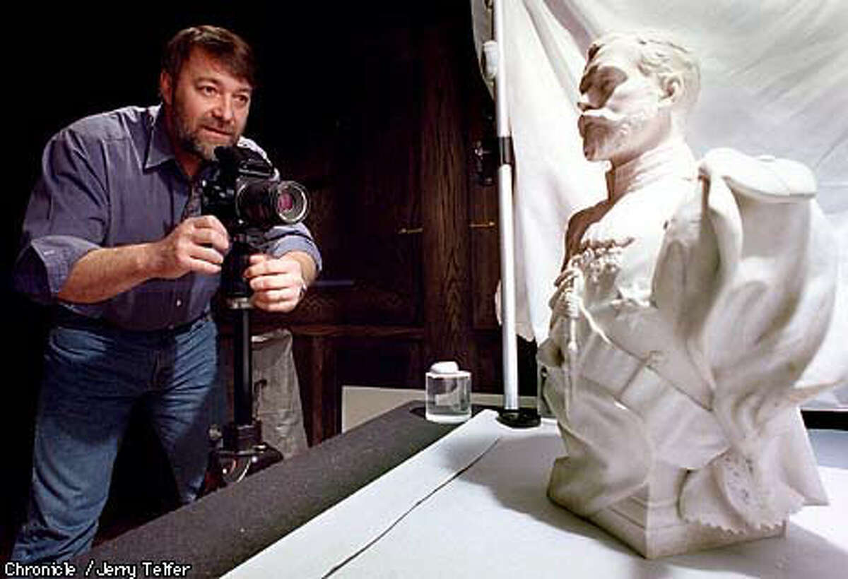Andre Ruzhnikov, a leading dealer in Russian art and in memorabilia of the Romanovs, photographed an alabaster bust of Czar Nicholas II. Chronicle Photo by Jerry Telfer