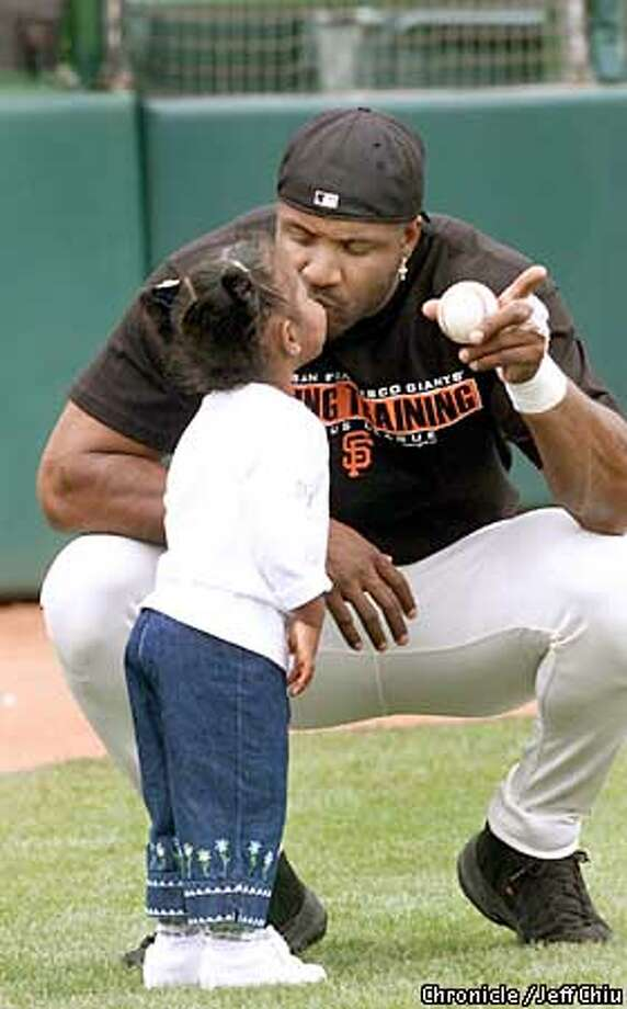 Barry Bonds gets a kiss from his daughter Aisha Lynn during warmups before the Giants beat the A's 4-2 on Monday afternoon in Scottsdale, AZ. Photo by Jeff Chiu / The Chronicle. Photo: Jeff Chiu