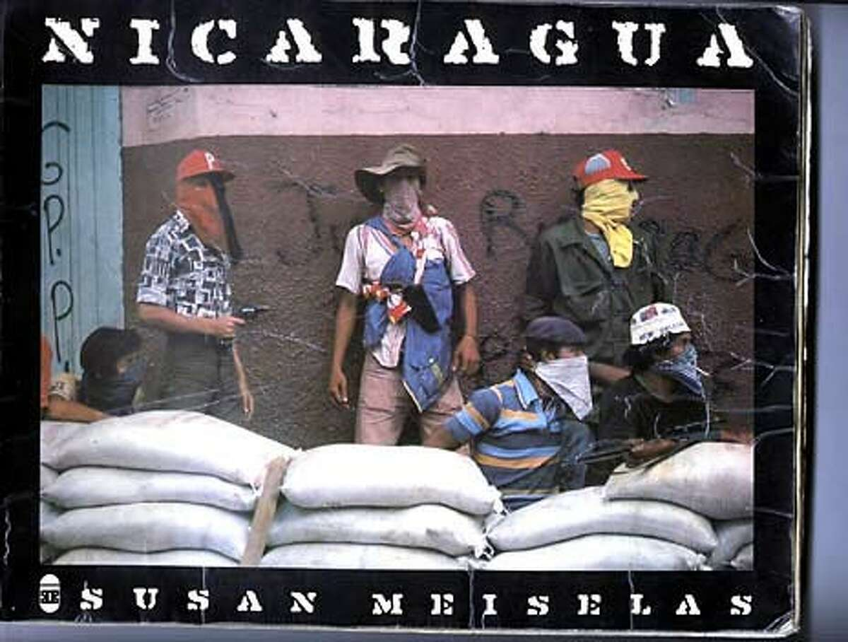 """Susan Meiselas' picture of a Sandinista rebel in the 1979 Nicaraguan revolt became a symbol of the insurrection. She made notes in the margins years later when she returned to track down the subject. The photograph, and her series, were made into a book, """"Nicaragua,"""" which includes a cover shot from the revolution. Susan Meiselas photography"""