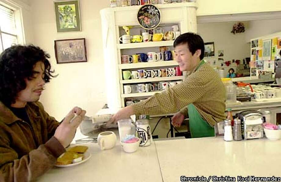 WBEDDIES23-C-15FEB01-SF-CH  CHRISTINA KOCI HERNANDEZ/CHRONICLE  At Eddie's Cafe (a soul food restaurant), on Divisadero in San Francisco, owner Min Huang (R) hands the paper to regular, Vern McAllister, (L)who lives in the neighborhood. Photo: CHRISTINA KOCI HERNANDEZ