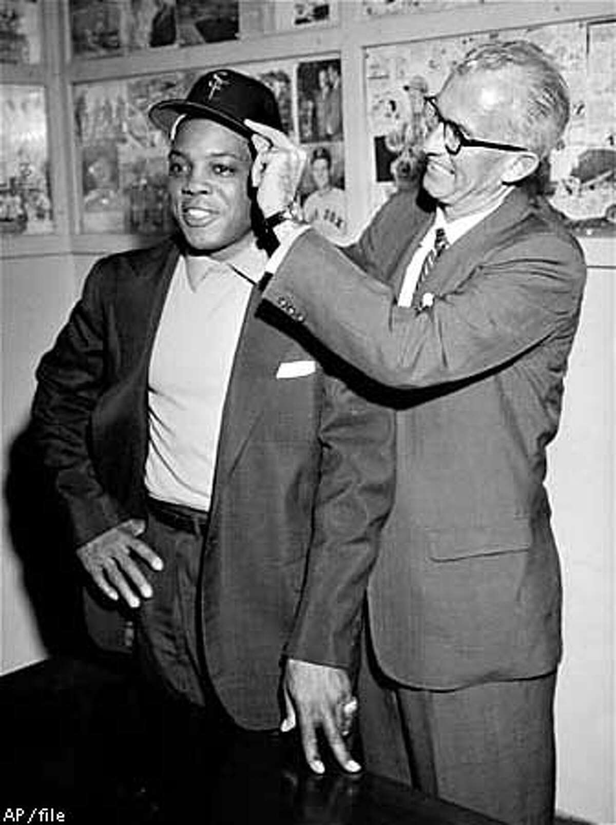 """Manager Bill Rigney, right, places a San Francisco Giants cap on Willie Mays during a press conference at Seals Stadium, October 31, 1959. Willie's first exclamation when he viewed the field was a smiling, """"This park's too big, man,"""" and added, """"It will take a good belt for a home run."""" (AP Photo/stf)"""