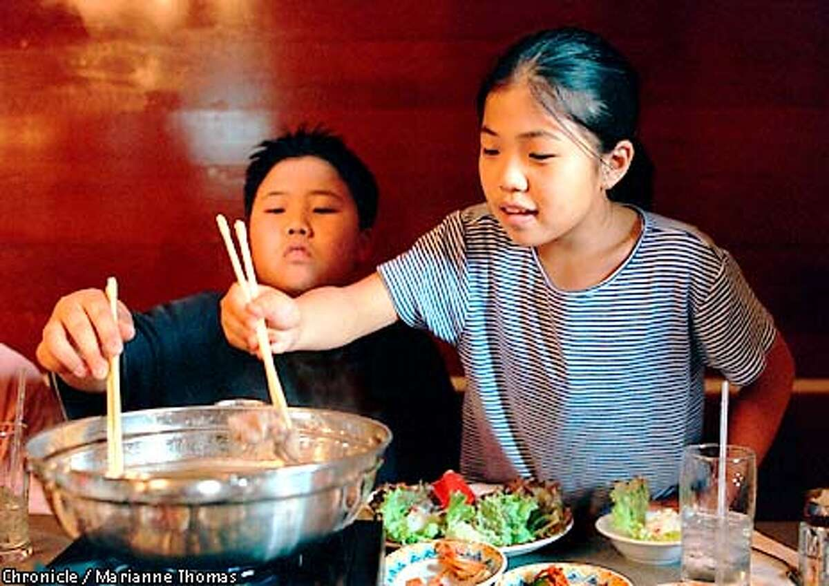 April Kim, 10, and her brother, Sean, 12, serve themselves shabu shabu�a traditional Korean dish of thinly sliced beef dipped in �sh broth and wrapped with rice in lettuce�at the grand opening of Jong Ga House, a Korean restaurant on Grand Avenue in Oakland. COURTESY
