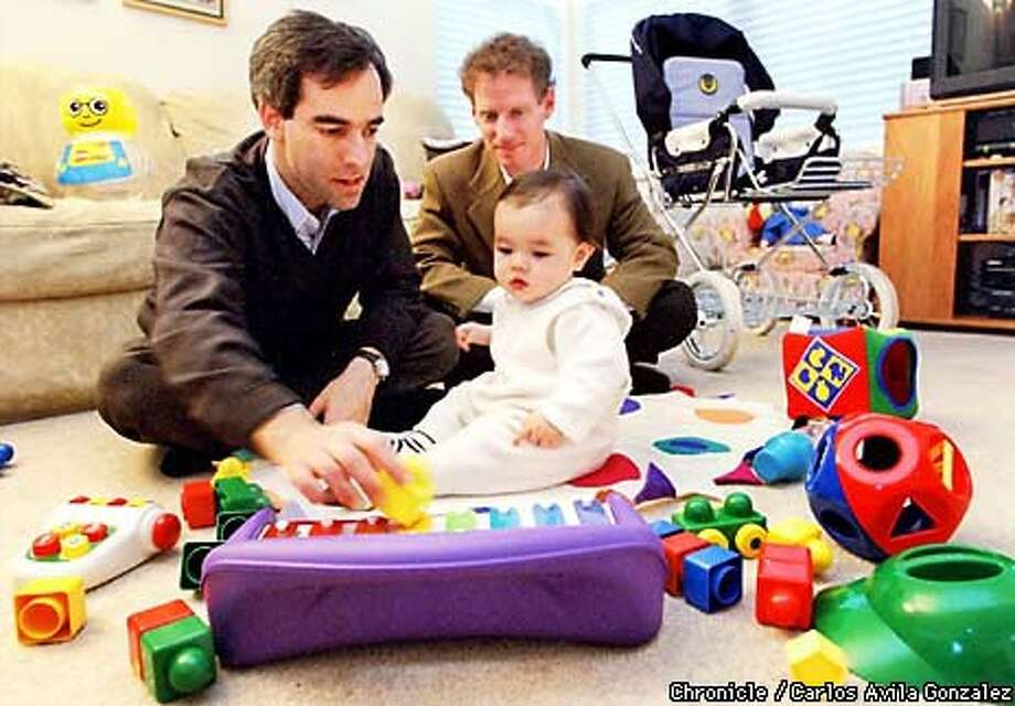 Matt Glickman (left) played with his 10-month-old daughter, Emma, while BabyCenter co-founder Mark Selcow watched.  Chronicle Photo by Carlos Avila Gonzaelez