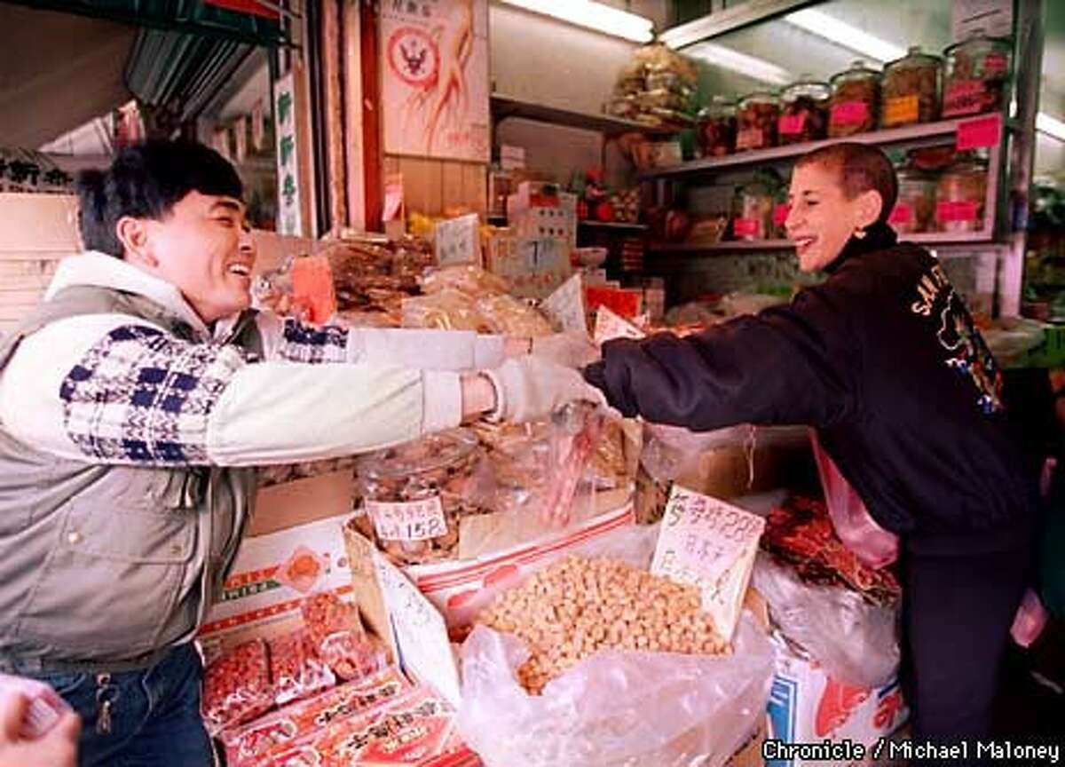 A day in Chinatown finds Tropp speaking Mandarin with a shopkeeper. Chronicle Photo by Michael Maloney