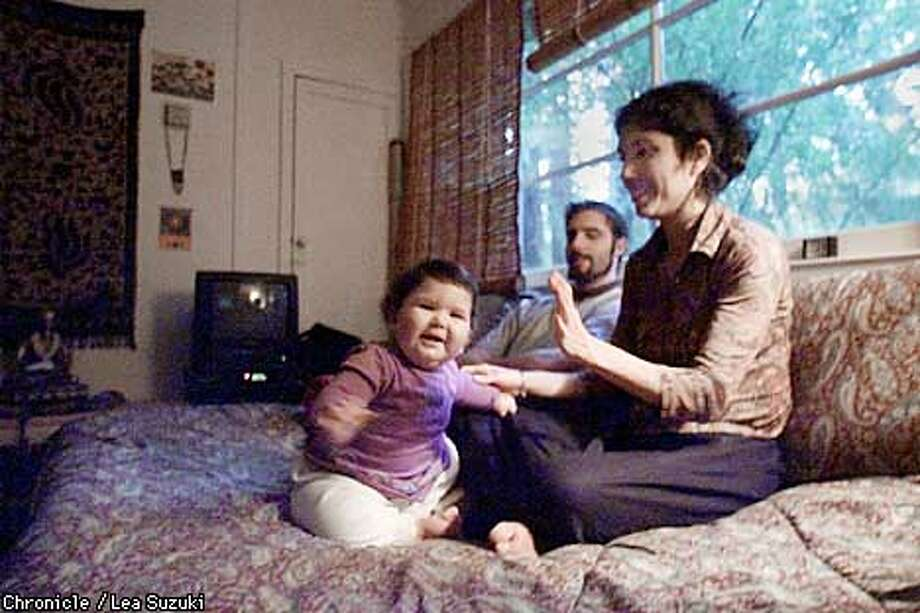 From left: Radha Luna Smith, 11 months; Subal Smith and Tulsi Briones. Radha sits with her parents in their living room near Santa Cruz. Both Subal Smith and Tulsi Briones were raised as Hare Krishna while growing up. Photo By Lea Suzuki Photo: LEA SUZUKI