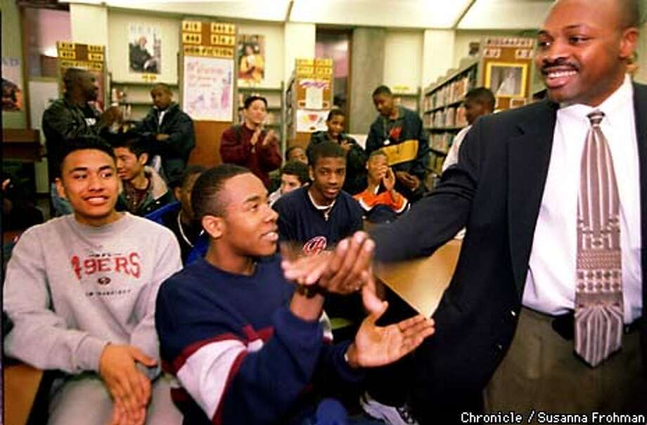 =Richmond High School basketball coach Ken Carter, right, congratulates his team members, including junior Montague Christian, after announcing that the team would be allowed to resume playing basketball. Team members will continue to meet in the library for daily tutoring in order to keep their grades up to the coach's standards.  BY SUSANNA FROHMAN/THE CHRONICLE Photo: SUSANNA FROHMAN