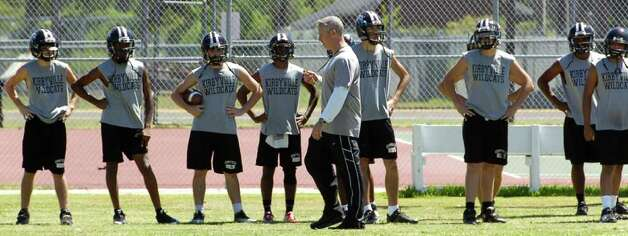 Kirbyville High School head football coach Greg Neece, center, gives instructions to his players before they do some running Tuesday morning.  Neece will coach his team against Vidor's Jeff Mathews on Friday night. Mathews and Neece worked together in 2000 at Vidor High School and have remained friends ever since.      Dave Ryan/The Enterprise Photo: Dave Ryan