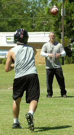 Kirbyville High School head football coach Greg Neece, right, works one-on-one with his quarterback and center Tuesday morning.  Neece will coach his team against Vidor's Jeff Mathews on Friday night. Mathews and Neece worked together in 2000 at Vidor High School and have remained friends ever since.      Dave Ryan/The Enterprise Photo: Dave Ryan