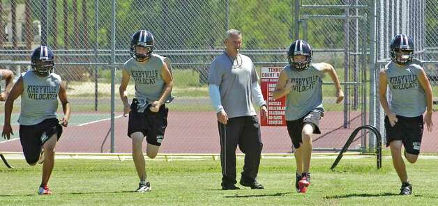 Kirbyville High School head football coach Greg Neece, center, blows his whistle for his players to do some running Tuesday morning.  Neece will coach his team against Vidor's Jeff Mathews on Friday night. Mathews and Neece worked together in 2000 at Vidor High School and have remained friends ever since.      Dave Ryan/The Enterprise Photo: Dave Ryan