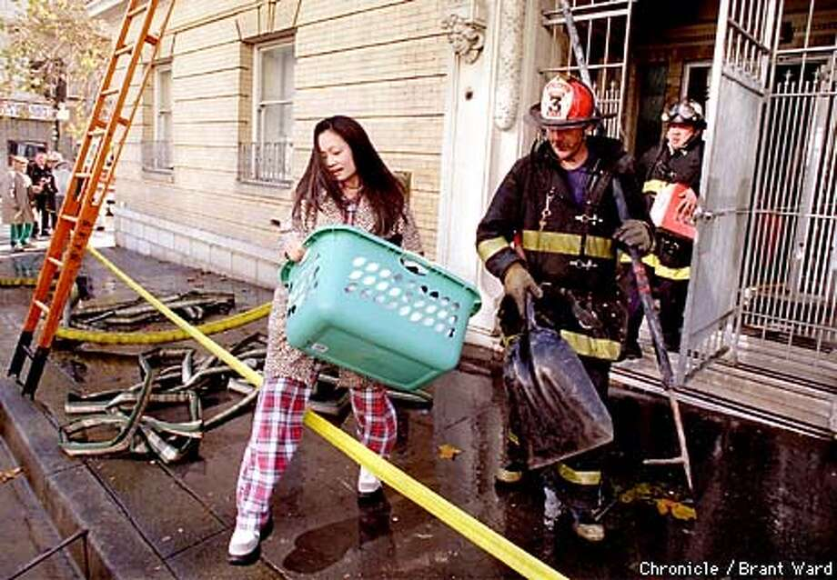 SF FIRE1/03JAN98/MN/BW--An unidentified resident of 901 Bush Street was able to remove some of her belongings as firemen mopped up after a 3-alarm fire gutted this downtown building making about 70 residents homeless for a while. By Brant Ward/Chronicle Photo: BRANT WARD