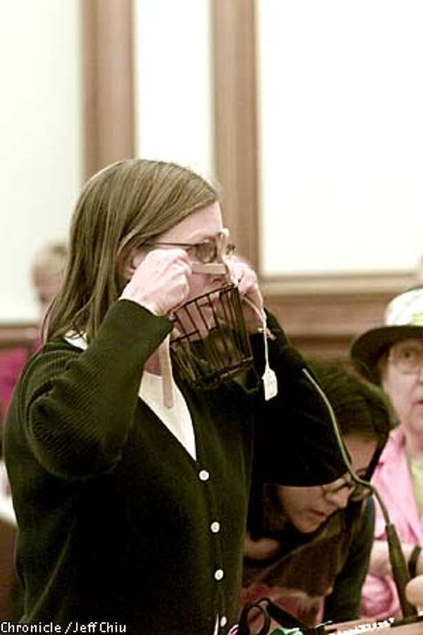"""Cindy Marabito of Reunion Rescue puts a muzzle on her face while speaking against a city proposal aimed at large, aggressive dogs. San Francisco's animal commission overwhelmingly rejected a proposal last night that would have required """"aggressive dogs"""" to be muzzled in public. Chronicle photo by Jeff Chiu"""