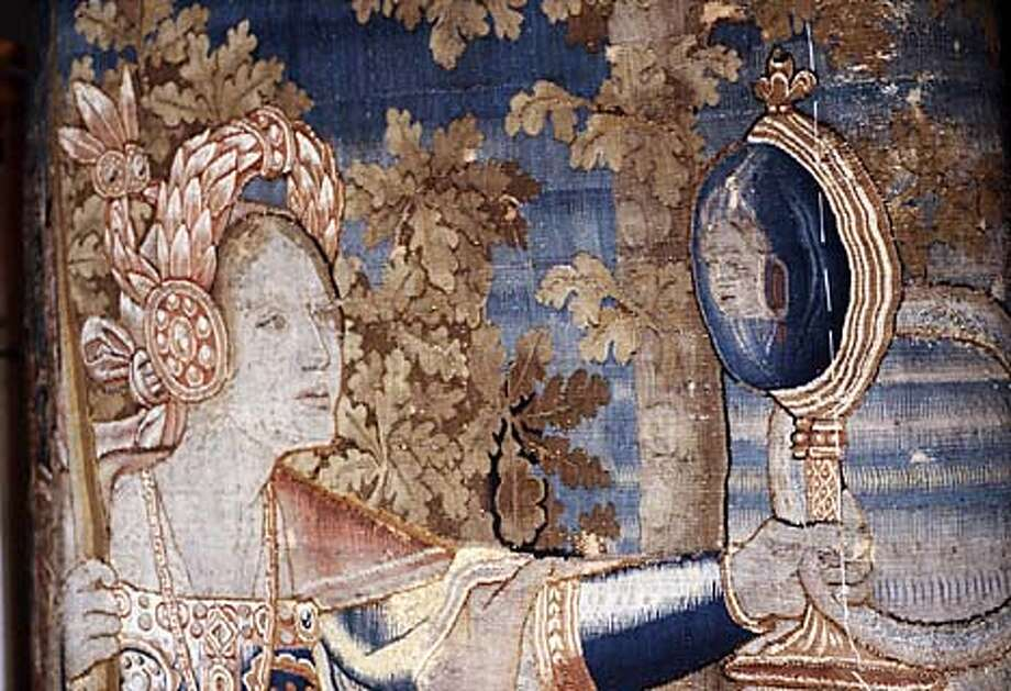 "The allegorical figure Prudence looks at her image in a mirror in a section of the tapestry ""The Triumph of Prudence."" Handout Photo"