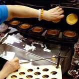 A worker removes the baked cookie off a hot plate to fold a fortune into to make fortune cookies at Golden Gate Fortune Cookies in China Town.  BY ROBIN WEINER/THE CHRONICLE