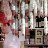 Molinari Deli worker, Maurizio Arcidiacono hurries past the a wide aray of dried salami that hangs from the ceiling of Joe Mastrelli's North Beach deli. BY MIKE KEPKA/THE CHRONICLE
