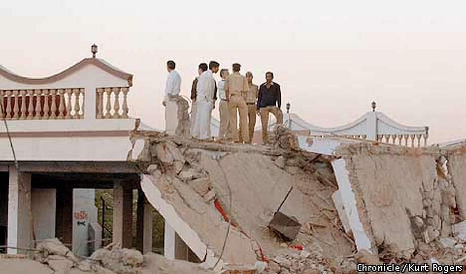 The group of geologist's look over damage to this house on the out side of the satellite district of Ahmadabad five people parish ed in it Photo By Kurt Rogers Photo: Kurt Rogers