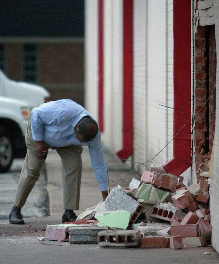 A man looks at a hole in the front of a Fiesta market after something smashed into it damaging a pharmacy at the store in an apparent robbery Thursday, Feb. 2, 2012, in Houston. A pharmacy worker said it appears that about $2,000 in cash was stolen, along with some drugs, and that the pharmacy had been rummaged through. Photo: Cody Duty, Houston Chronicle / © 2011 Houston Chronicle