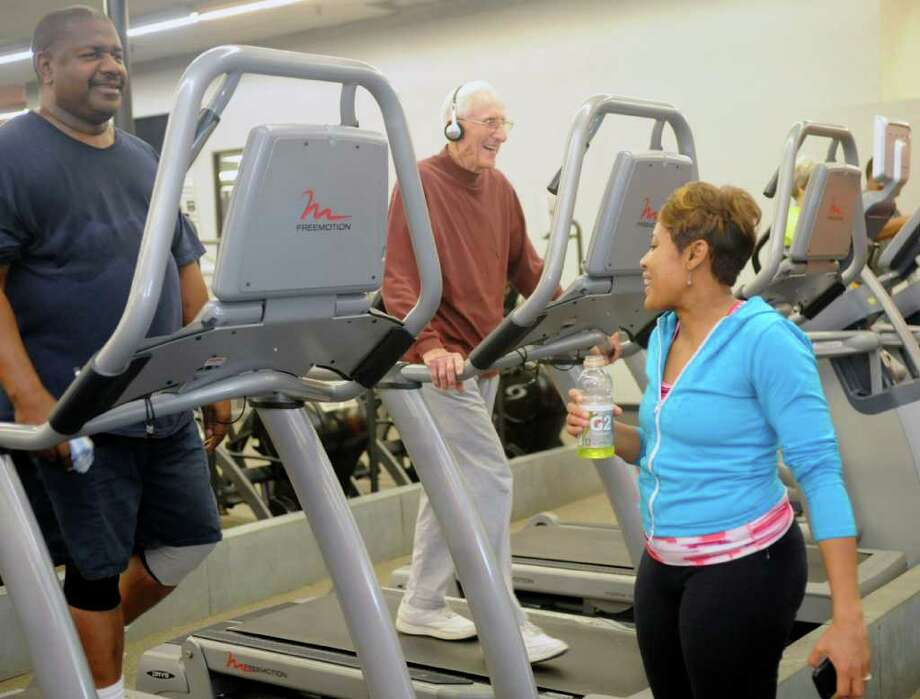 Jackie Simien, right, who works at KBMT Channel 12, talks with Al Prosser, middle, after getting off her treadmill during a Thursday morning workout at World Gym.  A lot of times when she is out in public, Simien will be stopped and asked to pose for pictures or give an autograph.   Dave Ryan/The Enterprise Photo: Dave Ryan