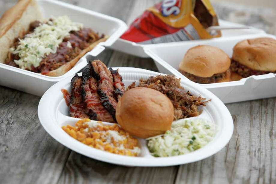 Food from The Smoke Shack food truck is seen Wednesday afternoon Jan. 25, 2012 near the intersection of Loop 410 and Nacogdoches. The food includes:  -- the Big Dog (sausage, brisket and pulled pork on a hoagie roll), left. -- Frito Pie (with chopped brisket), back. -- 2-meat plate (this one with brisket and pulled pork, w/ sides of corn, and cole slaw), front. -- Sliders, right.  (William Luther/wluther@express-news.net) Photo: William Luther, San Antonio Express-News / © 2012 SAN ANTONIO EXPRESS-NEWS