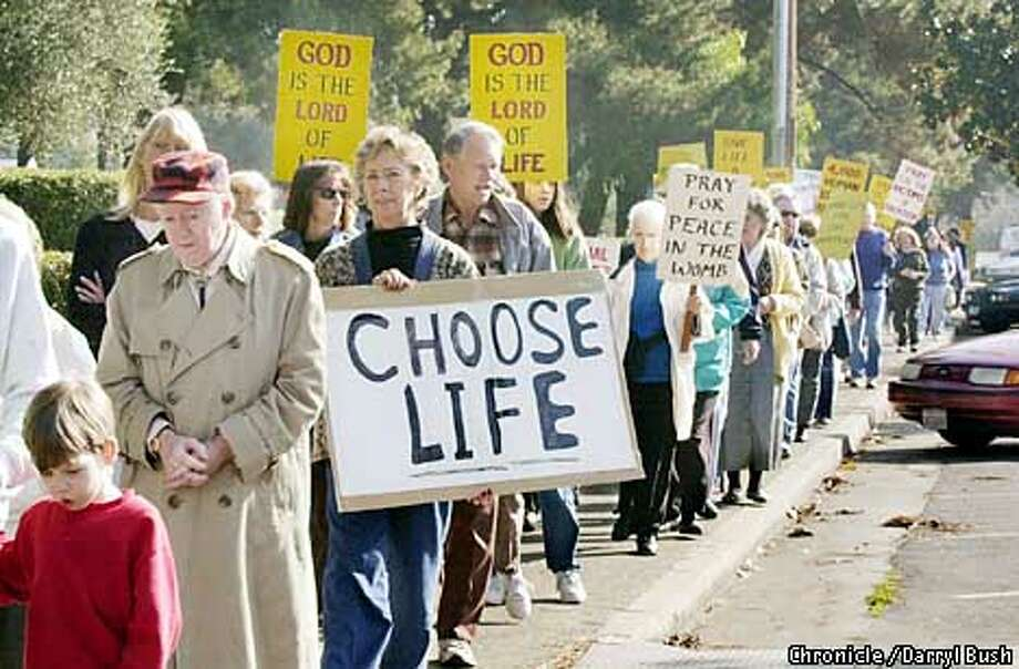 "One-hundred or more people, many members of Saint Nicholas Church in Los Altos, take part in a ""Pro-Life Prayer Walk"" as they walk down University Ave. in Los Altos on Monday. Diane O'Hearn of Sunnyvale holds ""Choose Life"" sign. Photo by Darryl Bush Photo: Darryl Bush"