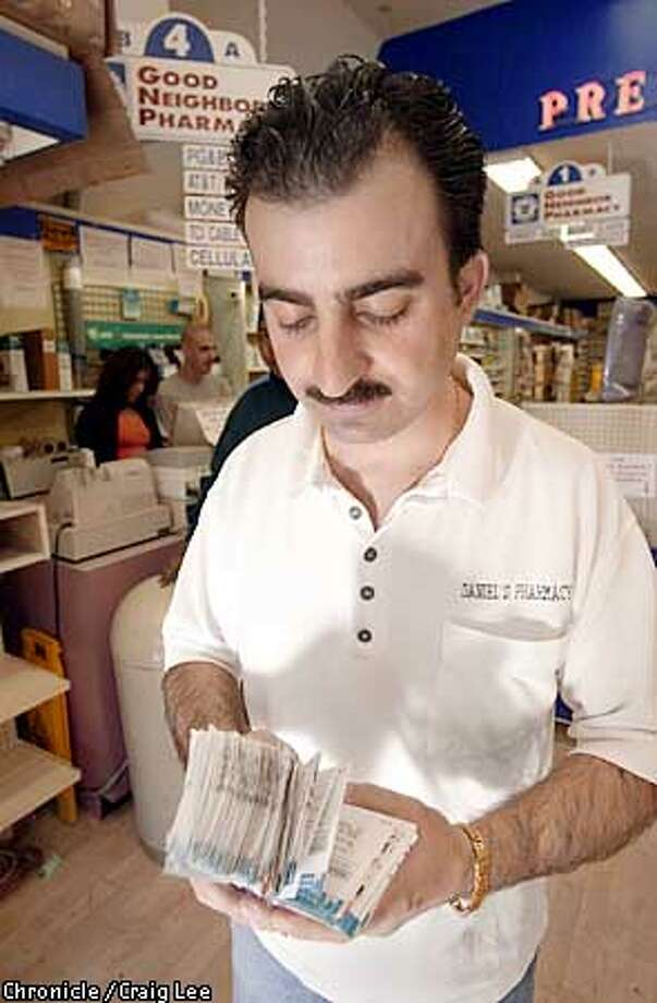 People paying their PG&E bills at Daniel's Pharmacy at 943 Geneva Avenue, it's one of the places you can go in and pay in person. Photo of Marwan Nasrah (that is the correct spellinf of his name, his first name is not Marvin), with a stack of PG&E bills paid at the Daniel's Pharmacy.  Photo by Craig Lee/Sann Francisco Chronicle Photo: CRAIG LEE