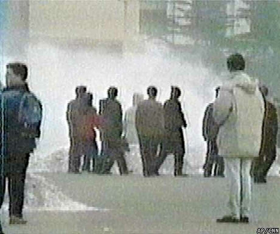 In this image taken from video, smoke rises from the scene where five Falun Gong worshippers set themselves on fire in Beijing's Tiananmen Square on Tuesday, Jan. 23, 2001 in a suicide attempt that left one sect member dead and the other four injured. The attempted group suicide is the latest in a series of increasingly brash actions by sect members defying the communist government's 18-month-long ban on Falun Gong. (AP Photo/CNN)
