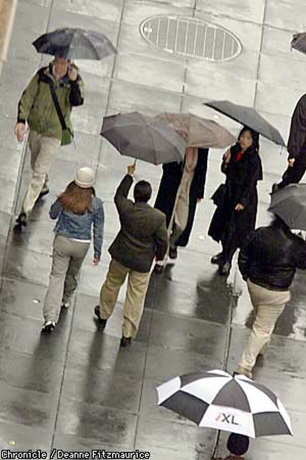 People maneuver their umbrellas to avoid collisions on the sidewalk along Bush Street in San Francisco's financial district at lunch time as a rainstorm comes into the Bay area.  CHRONICLE PHOTO BY DEANNE FITZMAURICE Photo: DEANNE FITZMAURICE