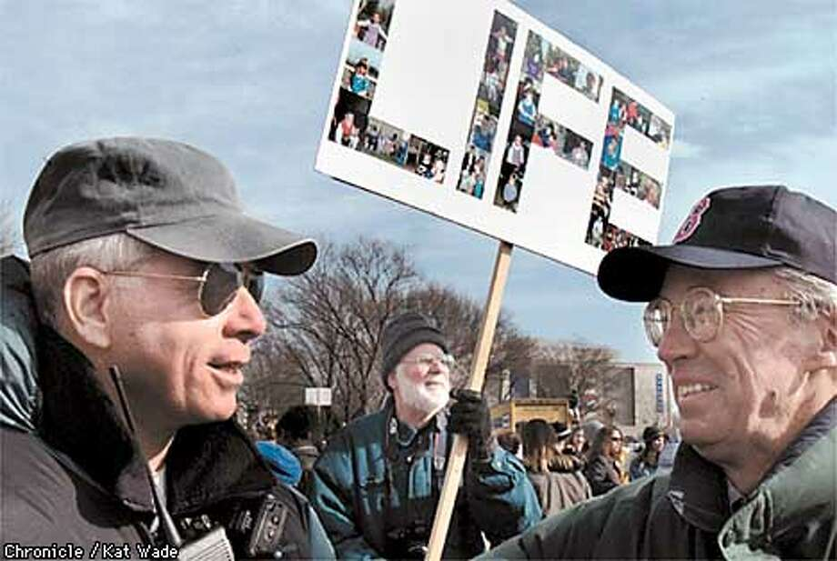 Gregg Cunningham, of the Center for Bio-Ethical Reform in Los Angelas, talks with T.J.Gallagher, anoth member of the coalition from Morristown, New Jersey, Jack Covert of Ship Bottom, New Jersey displays a sign of baby photos that spells out LIFE at the Washington Monument before the march up Constitution Avenue in Washington D.C. to protest the Supreme Court 1973 Roe vs Wade decision. SAN FRANCISCO CHRONICLE BY KAT WADE Photo: KAT WADE