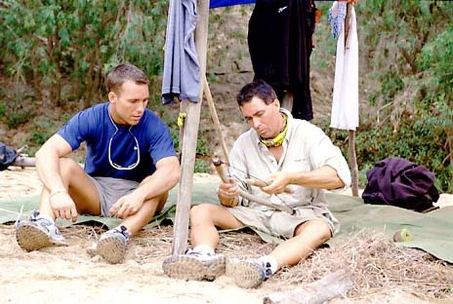 SURVIVOR: THE AUSTRALIAN OUTBACK contestant Colby Donaldson watches as Keith Famie works on the Ogakor tribe's fire making equipment.  Photo: Monty Brinton/CBS  HANDOUT Photo: HANDOUT