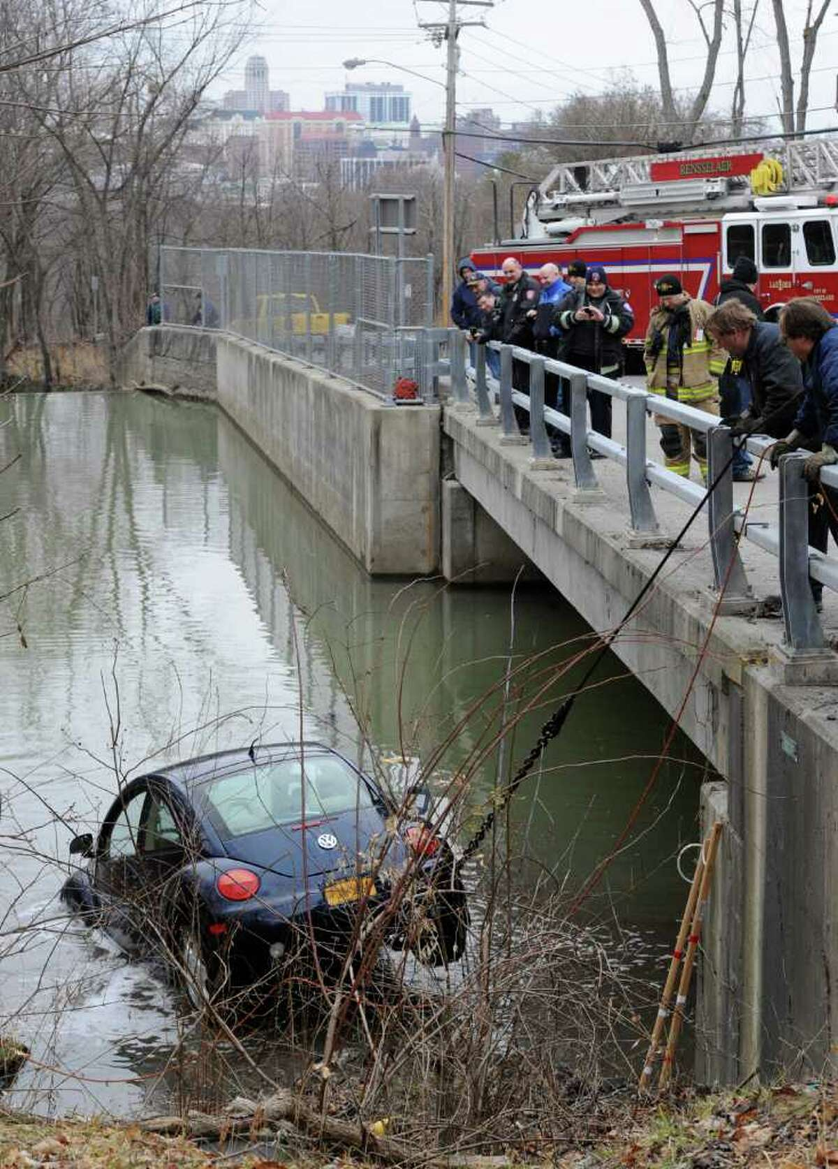 Members of the Clinton Heights Fire Department Rescue Squad work to remove a Volkswagen bug from the depths of the Red Mill Creek in Rensselaer, N.Y. Feb. 2, 2012. Geist towing was used to winch the vehicle from the creek. (Skip Dickstein / Times Union)