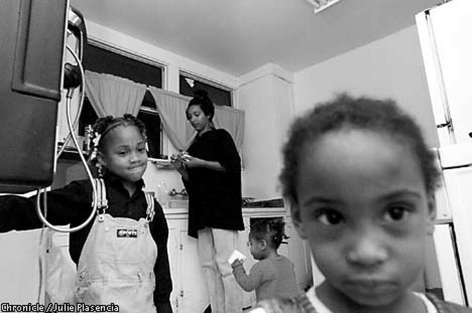 Shannell Flowers fixed dinner for daughters (left to right) Sharnell, 6, Leeane, 1, and Lakia, 3, in the Oakland halfway house now home to them.  Chronicle photo by Julie Plasencia
