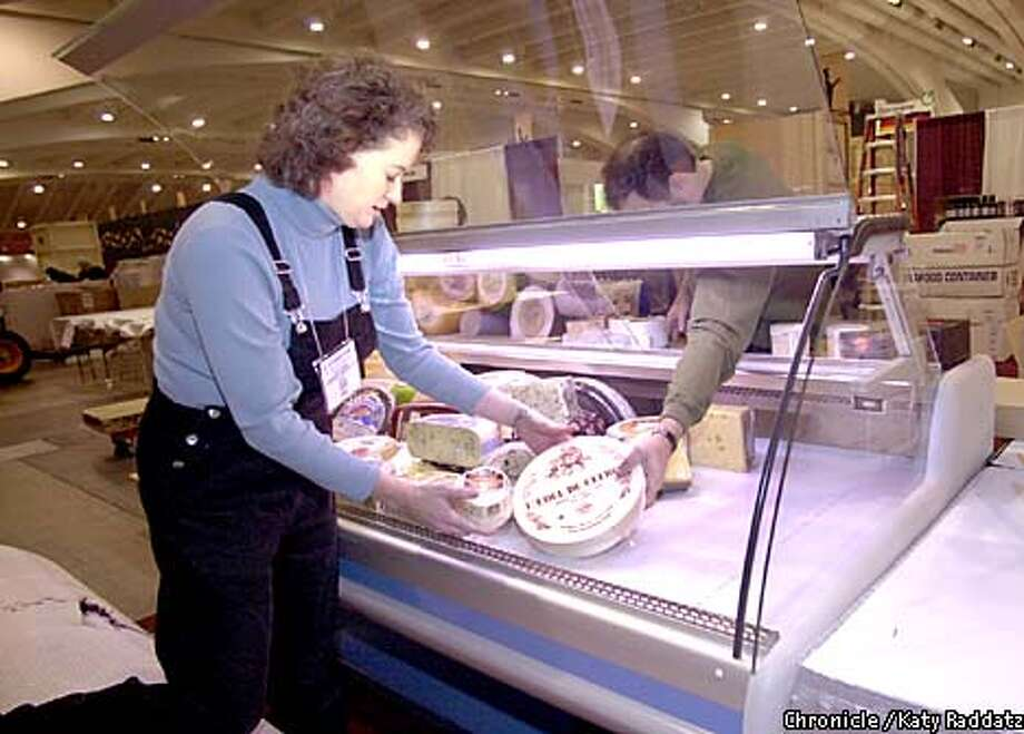 Trish Pohanka and Jeff Binstein arrange a cheese display at Moscone Center, which is exempt from power outages. Chronicle photo by Katy Raddatz