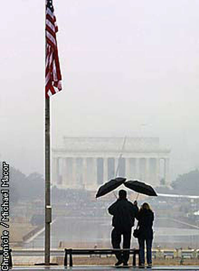 Despite the drizzle in Washington, a couple stopped to take a picture of the Lincoln Memorial. Chronicle photo by Michael Macor