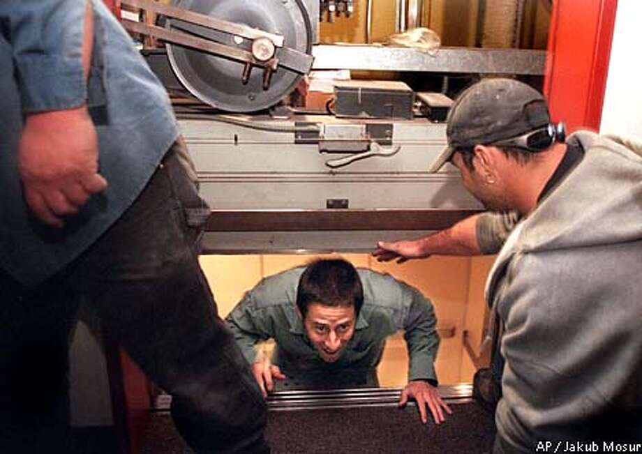 Law student Jesse Sisgold got stuck in an elevator between floors at Hastings College in San Francisco during the rolling blackout Wednesday. Dan Gruber, right, helped him out. Associated Press photo by Jakub Mosur
