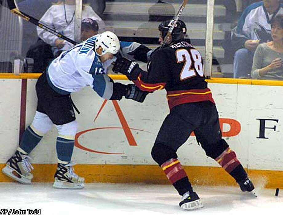 San Jose Sharks Alexander Korolyuk, left, and Calgary Flames Robyn Regehr battled along the boards for the puck in the first period. Associated Press photo by John Todd