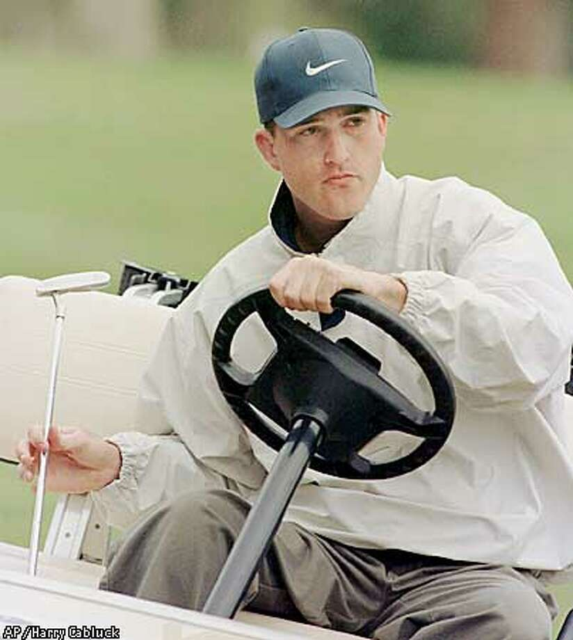 Nike Tour golfer Casey Martin holds a putter as he sits behind the wheel of a cart during pro-am play in the Greater Austin Open on Wednesday, March 4, 1998, in Austin, Texas. It will be his first tournament since a court ruled that he could use a cart in competetion. (AP Photo/Harry Cabluck) Photo: HARRY CABLUCK