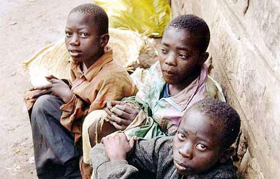 Three homeless boys huddled next to a wall in Nairobi; they are among the thousands of homeless children living on the streets of the capital. Photo by David Gough, special to The Chronicle