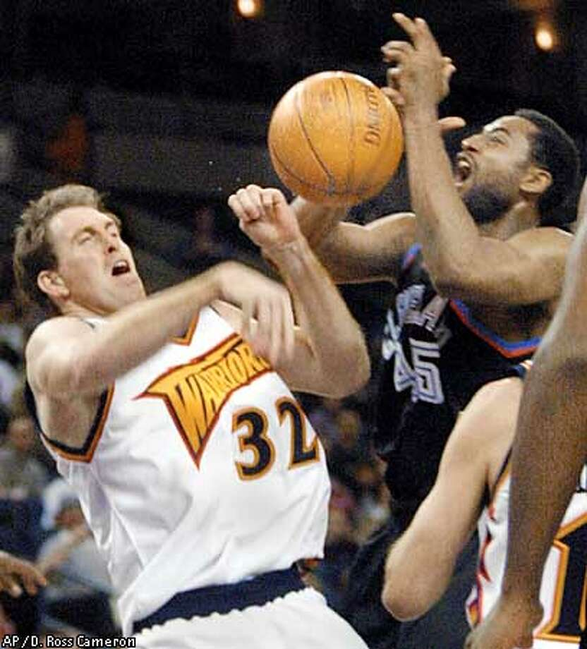Golden State Warriors' Adam Keefe, left, and Cleveland Cavaliers' Cedric Henderson collide during the fourth quarter Monday, Jan. 15, 2001, in Oakland, Calif. Keefe was called for the foul. The Cavaliers won the game, 107-101. (AP Photo/D. Ross Cameron) Photo: D. ROSS CAMERON
