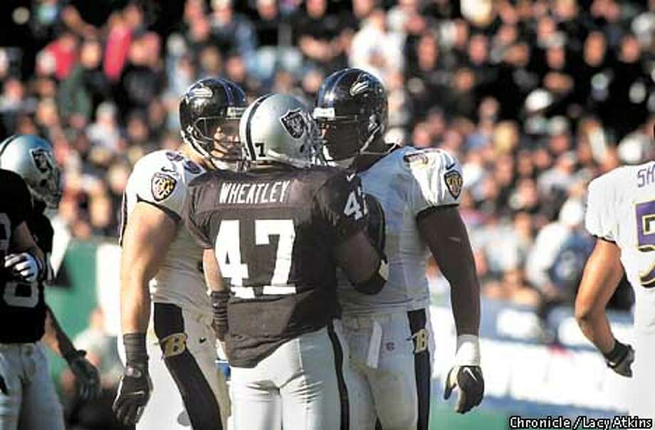 Tyrone Wheatley has words with defensive end Rob Burnett during the second quarter. The Oakland Raiders and the Baltimore Ravens battle for the AFC Championship on January 14, 2001 in Oakland, California. Lacy Atkins/San Francisco Chronicle Photo: Lacy Atkins