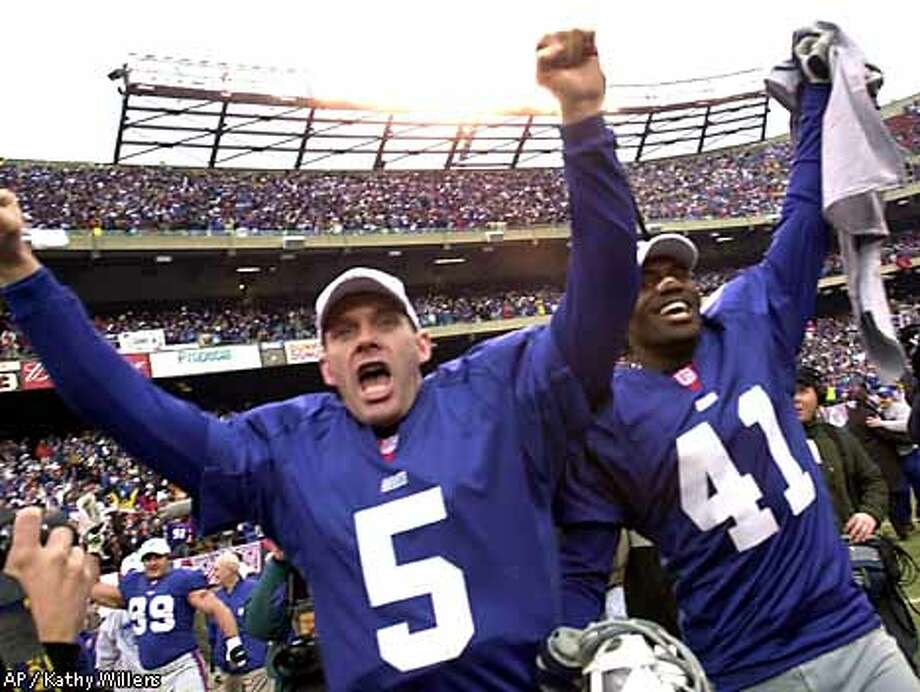 Giants quarterback Kerry Collins (5) and cornerback Dave Thomas were up in arms after the Giants steamrolled past the Vikings yesterday 41-0 to earn a ticket to the Super Bowl. Associated Press photo by Kathy Willens