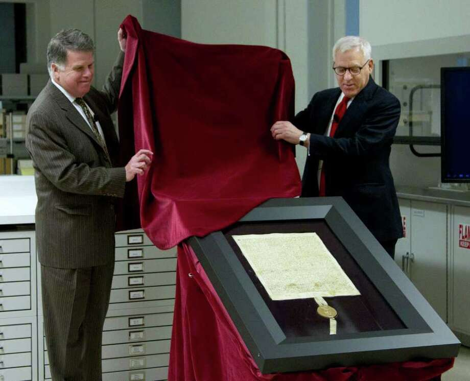 Carlyle Group co-founder and Magna Carta owner David Rubenstein, right, and Archivist of the U.S. David Ferriero, unveil the 1297 Magna Carta in its new state-of-the-art encasement at the National Archives in Washington, Thursday, Feb. 2, 2011.  (AP Photo/Manuel Balce Ceneta) Photo: Manuel Balce Ceneta