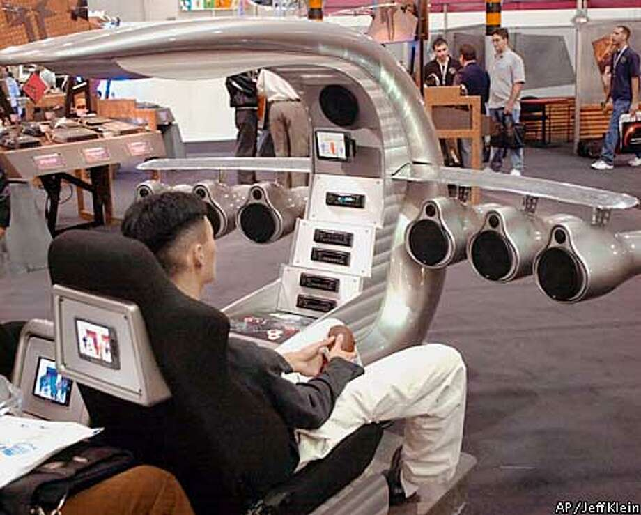 "A consumer makes himself comfortable in the ""Scorpion"" on Sunday, January 7, 2001, as he listens to music and watches a video at the Consumer Electronics Show at the Las Vegas Convention Center in Las Vegas. The Scorpion is a prototype of a futuristic vehicle and gave a demostration of how the rockford fosgate stereo digital audio system might sound. (AP Photo/Jeff Klein)"