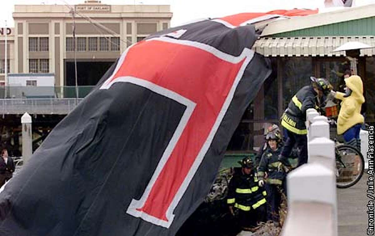 Oakland firemen come up from securing an Airship USA bilmp that went down on the roof of a local restaurant, The Oyster Reef, located on the Embarcadero in Oakland on January 9, 2000. (JULIE PLASENCIA/SAN FRANCISCO CHRONICLE)