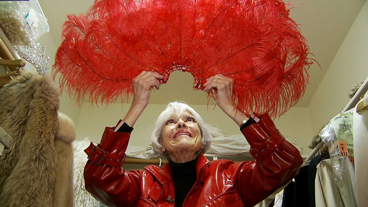 ?'Carol Channing looks at a feathered headdress from,