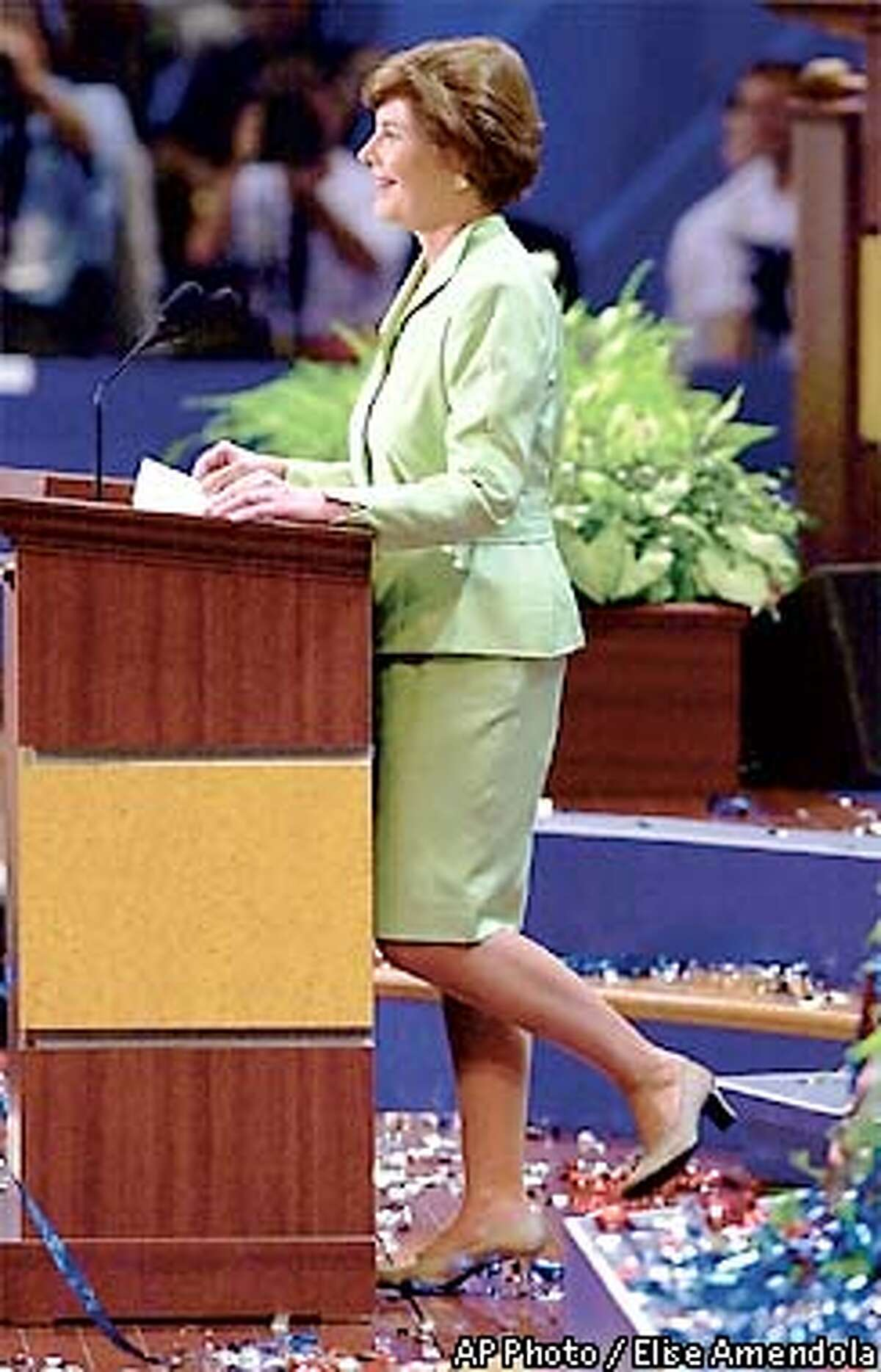 Texas first lady Laura Bush, wife of presidential hopeful George W. Bush, stands behind the podium amid confetti that was throw after she was introduced to delegates during the evening session of the Republican National Convention in Philadelphia on Monday, July 31, 2000. (AP Photo/Elise Amendola)